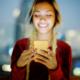 Handy- Laptop- und Elektronikversicherung: Lächelnde junge Frau ist glücklich mit einem Smartphone in der Hand, da sie eine Versicherung zum Schutz des Smartphones abgeschlossen hat.