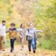 Angehörigen Schutz bei Todesfall: Junge Familie mit zwei Söhnen spazieren im Wald. Die Kinder rennen. Die Familie hat eine Versicherung für Angehörige bei Todesfall.