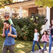 Gebäudeversicherung und Gebäudehaftpflicht: Eine Junge Familie mit 3 Kindern, der Sohn auf den Schultern des Vaters laufen glücklich aus dem Haus raus.