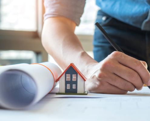 Eigenheim Finanzierung: Ein Mann mit eingerolltem Hausplan und einem kleinen Haus auf dem Tischt unterschreibt gerade seine Eigenheim Finanzierung.