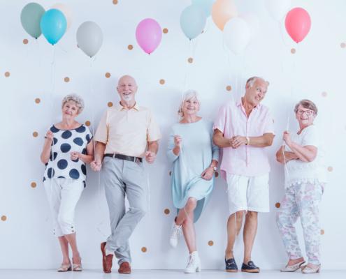 Pensionsplanung: Nach einer gut durchdachten Pensionsplanung erfolgt die Feier. Drei ältere Damen und zwei Herren posieren mit bunten Luftballons an einer weißen Wand und freuen sich über ihre Pensionierung.