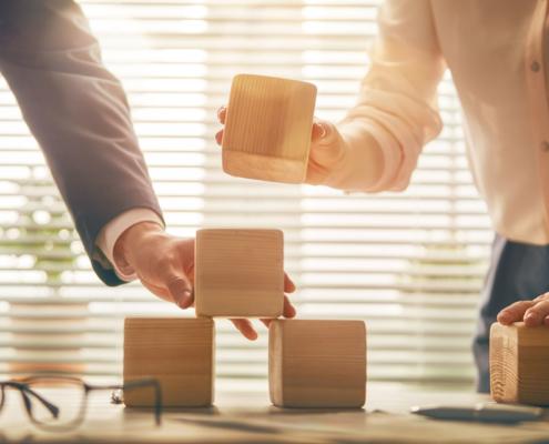 Betriebshaftpflicht: Zwei Personen legen Holzbausteine zusammen auf einem Tisch. Das Fundament einer guten Betriebshaftpflicht. Informieren Sie sich bei V&V Consulting GmbH.
