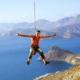 Extremsport Unfallversicherung: Ein Bergsteiger hängt glücklich am Seil mit beiden Daumen oben und Arme gestreckt. Im Hingergrund sind Gewässer und Gebirge zu sehen. Eine Extremsport Unfallversicherung ist unverzichtbar.