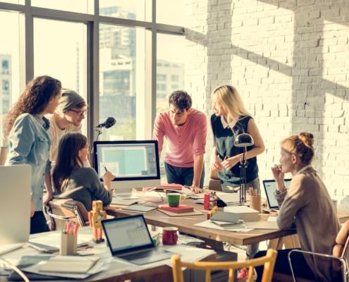 Selbstständigerwerbende beraten sich am Schreibtisch. Die Asset Management Group unterstützt Sie bei Finanzen und Versicherungen.