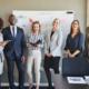 Für Unternehmen: Team eines Unternehmens posieren vor der Strategietafel und lächeln glücklich.