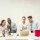 Mobbingversicherung: Vier Arbeitskollegen ziehen über einen Arbeitskollegen her. Eine Mobbingversicherung schützt Sie für den schlimmsten Fall.
