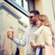 Privatkredit: Junges Paar mit Sonnenbrille und Kaffebechern To-Go in der Hand stehen am Schaufenster und denken über glücklich über einen Privatkredit nach für eine neue Anschaffung.