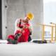 Unfallversicherung: Ein Arbeiter mit einem Helm auf dem Kopf, nebendran eine gestürzte Leiter. Er sitzt auf dem Boden und hält sich das Unterbein. Eine Unfallversicherung schützt gegen unvorhersehbare Ereignisse.