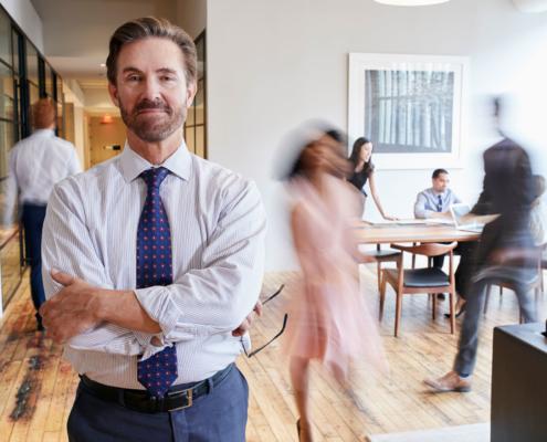 Die Vorsorge für Selbstständige muss vorsorglich bedacht werden. Dies weiß auch der selbstständige Mann mit Krawatte im Vordergrund und schaut im stehen in die Kamera, während sich die anderen Im Raum bewegen und arbeiten.